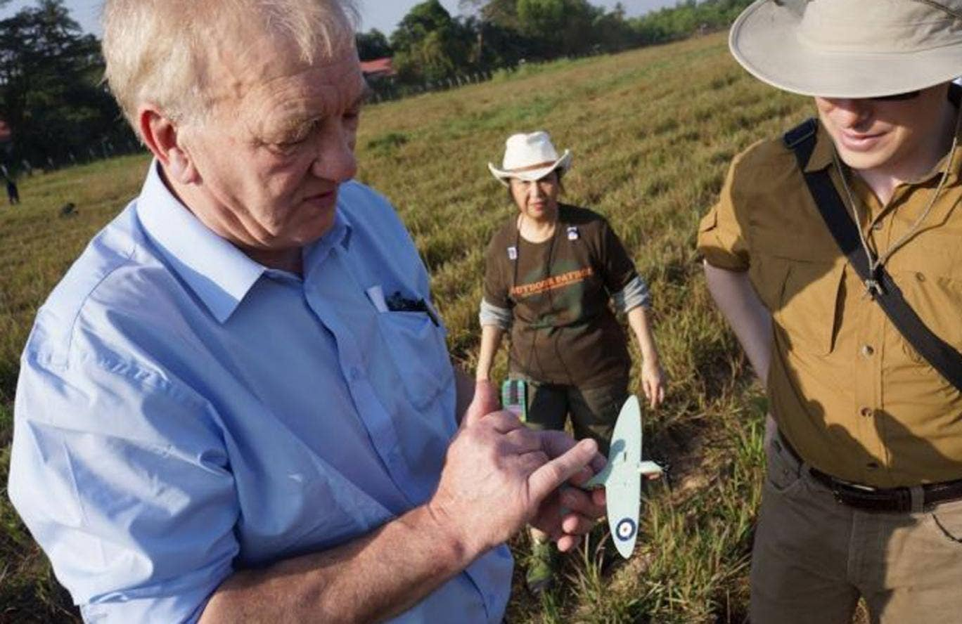 David Cundell holds a model Spitfire as he inspects a field in Burma earlier this month