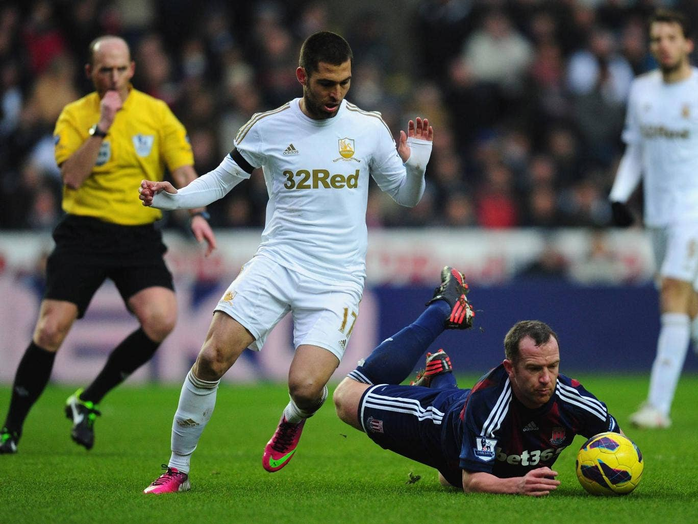 Stoke player Charlie Adam is fouled by Swansea player Itay Schechter