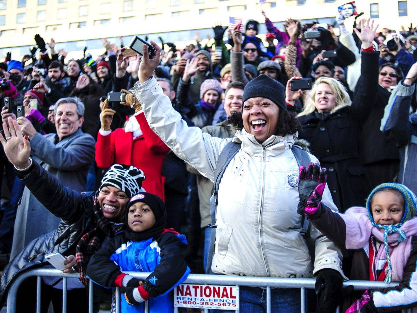 Spectators wave to President Barack Obama as the inaugural parade moves down Pennsylvainia Avenue