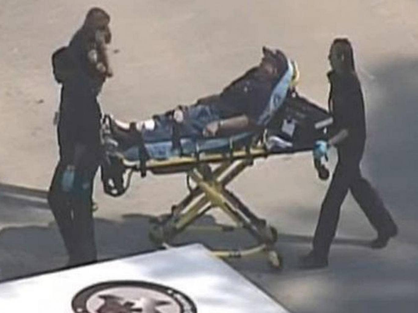 Police and emergency personnel evacuate an injured male on a stretcher outside a building on the Lone Star College Campus