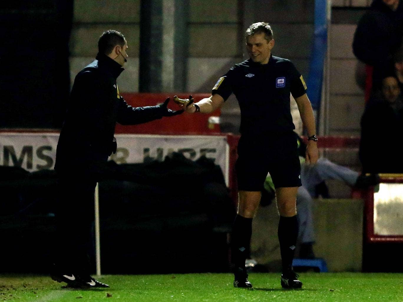 Referee Graham Scott removes a banana after being thrown on the pitch