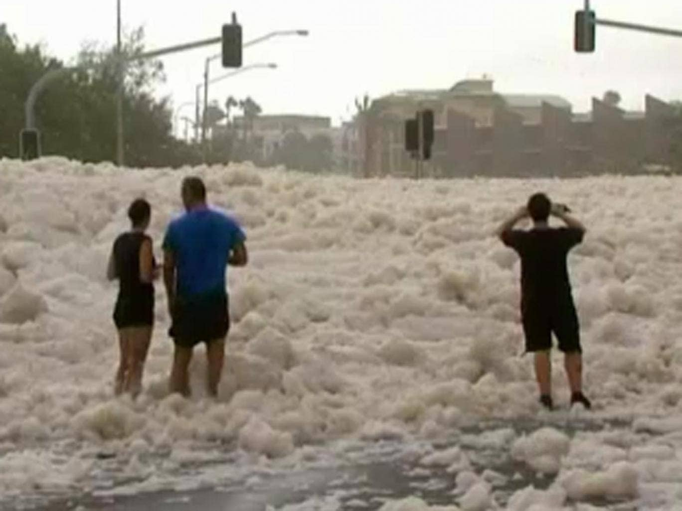 Residents look at the foam-covered streets