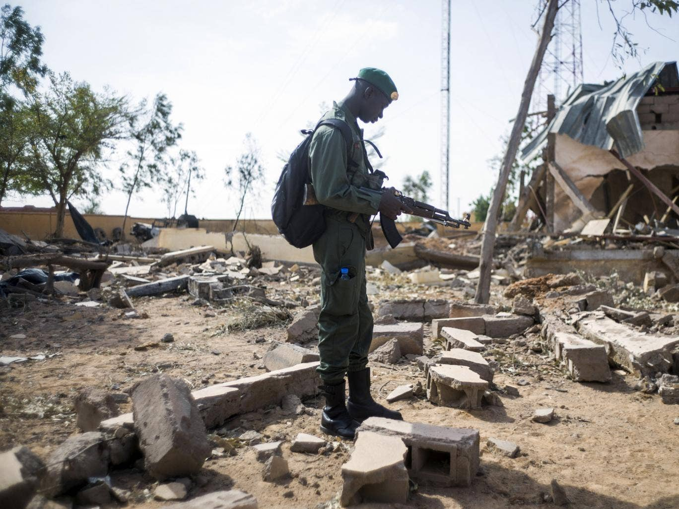 A Malian soldier stands in a destroyed area in the key central town of Konna now controlled by French and Malian army