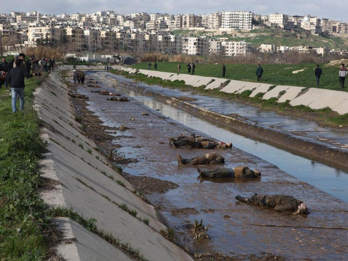 Locals gather at the banks of a small canal coming from a government-controlled suburb of Aleppo to view dozens of bodies of people