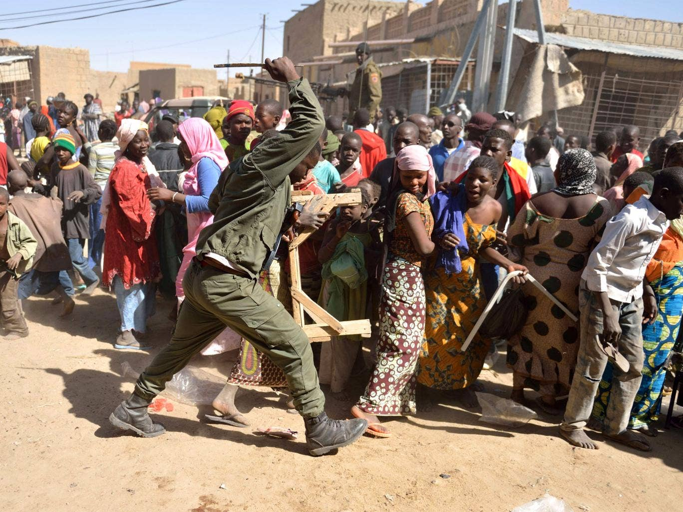 A Malian soldier trys to disperse looters in the streets of Timbuktu