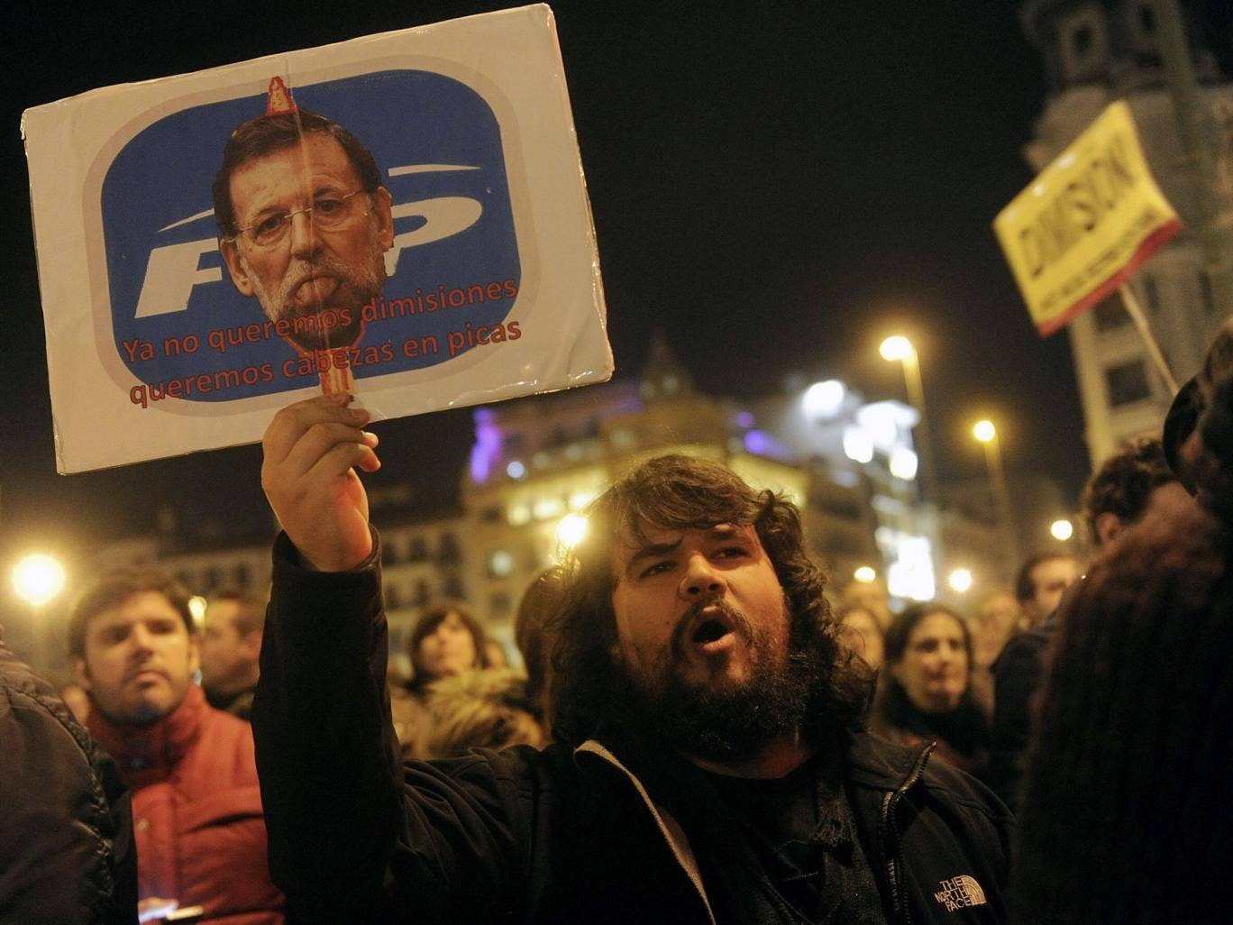 "January 31, 2013: A  man holds a placard depicting Spanish Prime Minister Mariano Rajoy and reading ""We don't even want resignations, we want heads on spike"" as he takes part in a demonstration against corruption scandals implicating the PP (Popular Party"