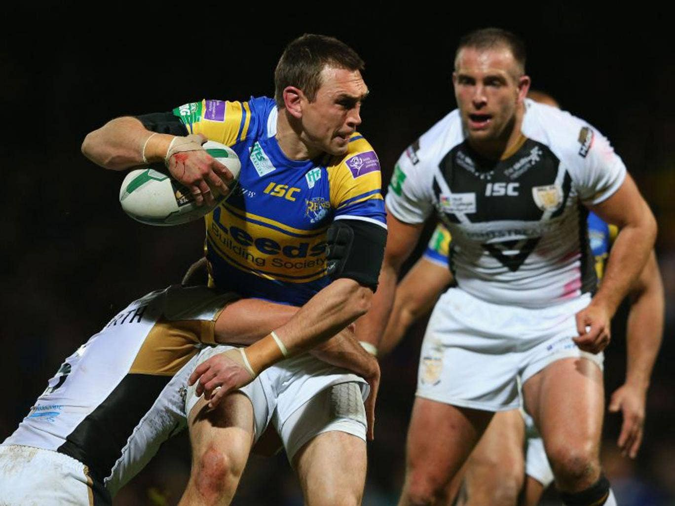 Leeds' Kevin Sinfield (left) is tackled by Hull's Daniel Holdsworth
