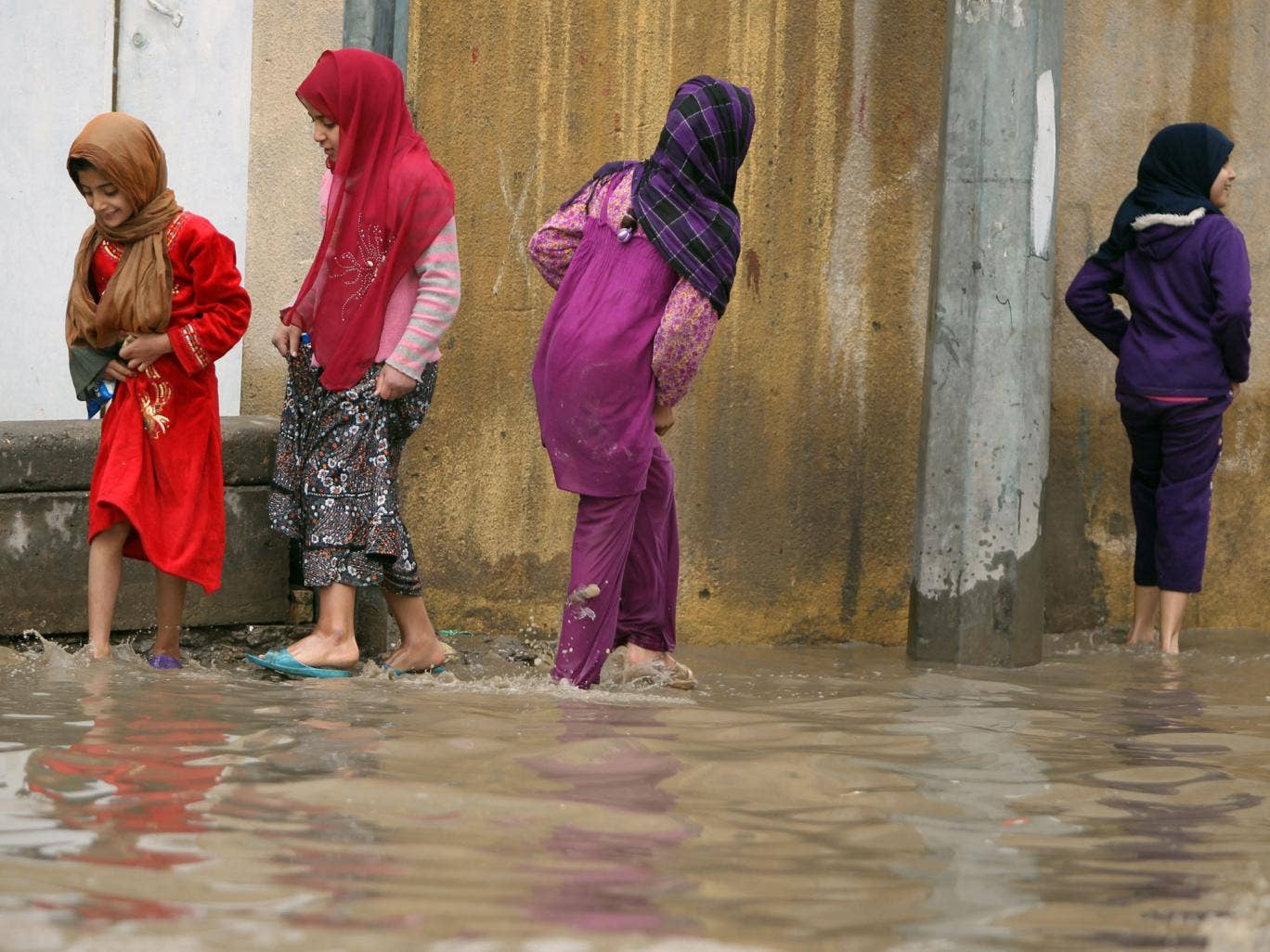 Deep water: Girls wade through Baghdad's flooded streets