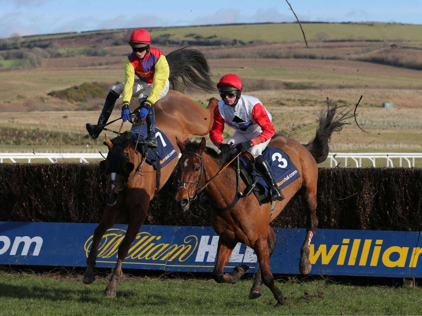 Jump lead: Nico de Boinville (right) on Carruthers moves ahead of Shaking Hands to win the West Wales National