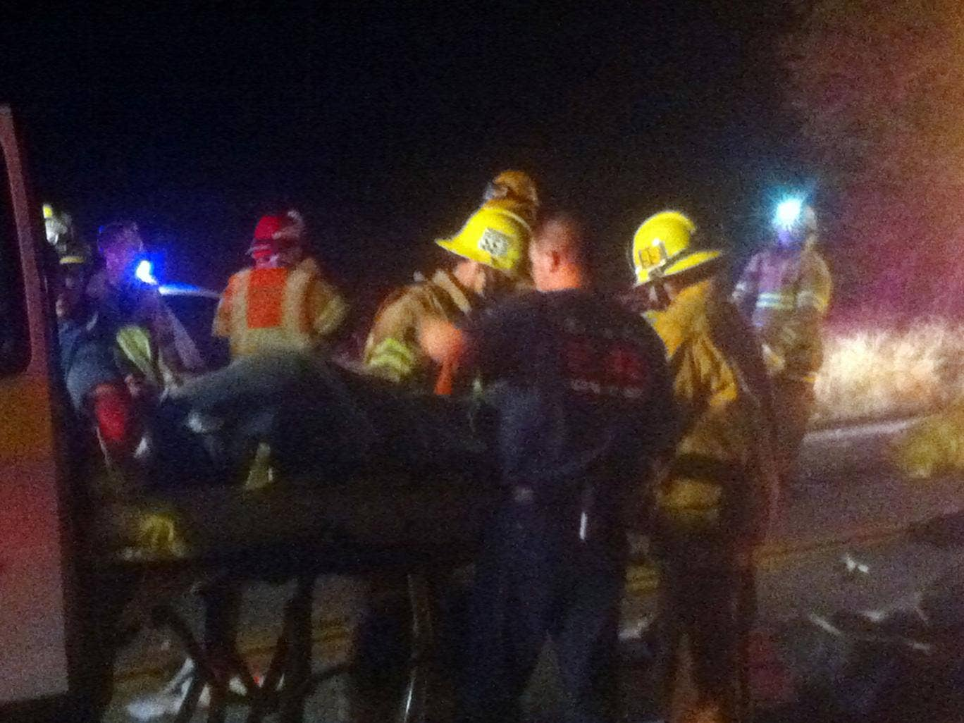 Emergency personnel assist victims at the scene of the bus crash near Forest Falls