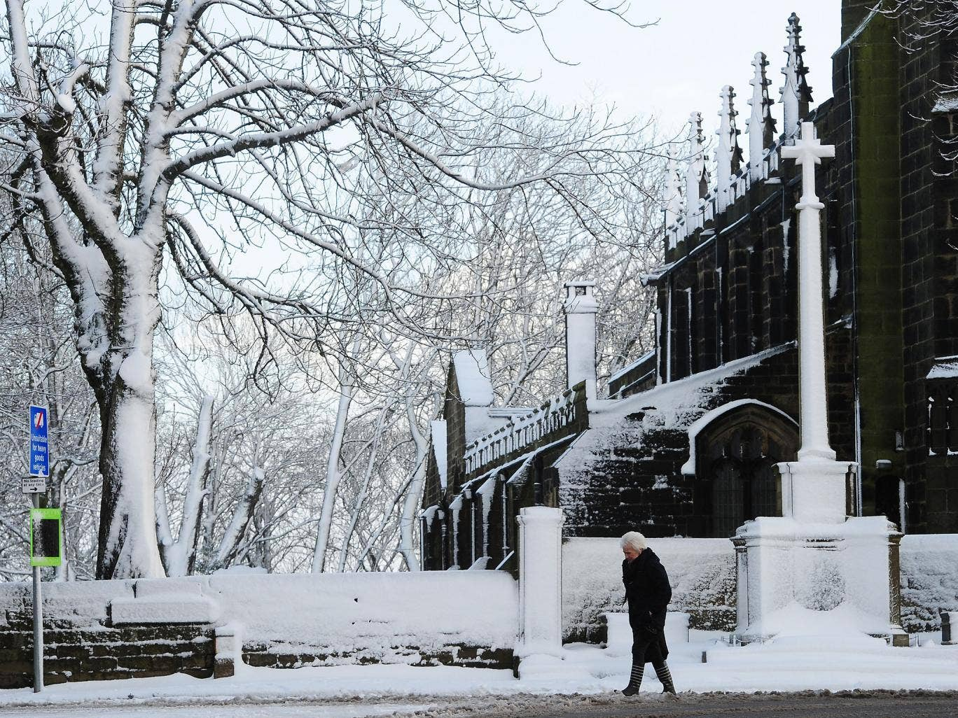 A woman makes her way past the St John the Baptist Church in Penistone, South Yorkshire, as parts of Britain brace for a return of snow and gales
