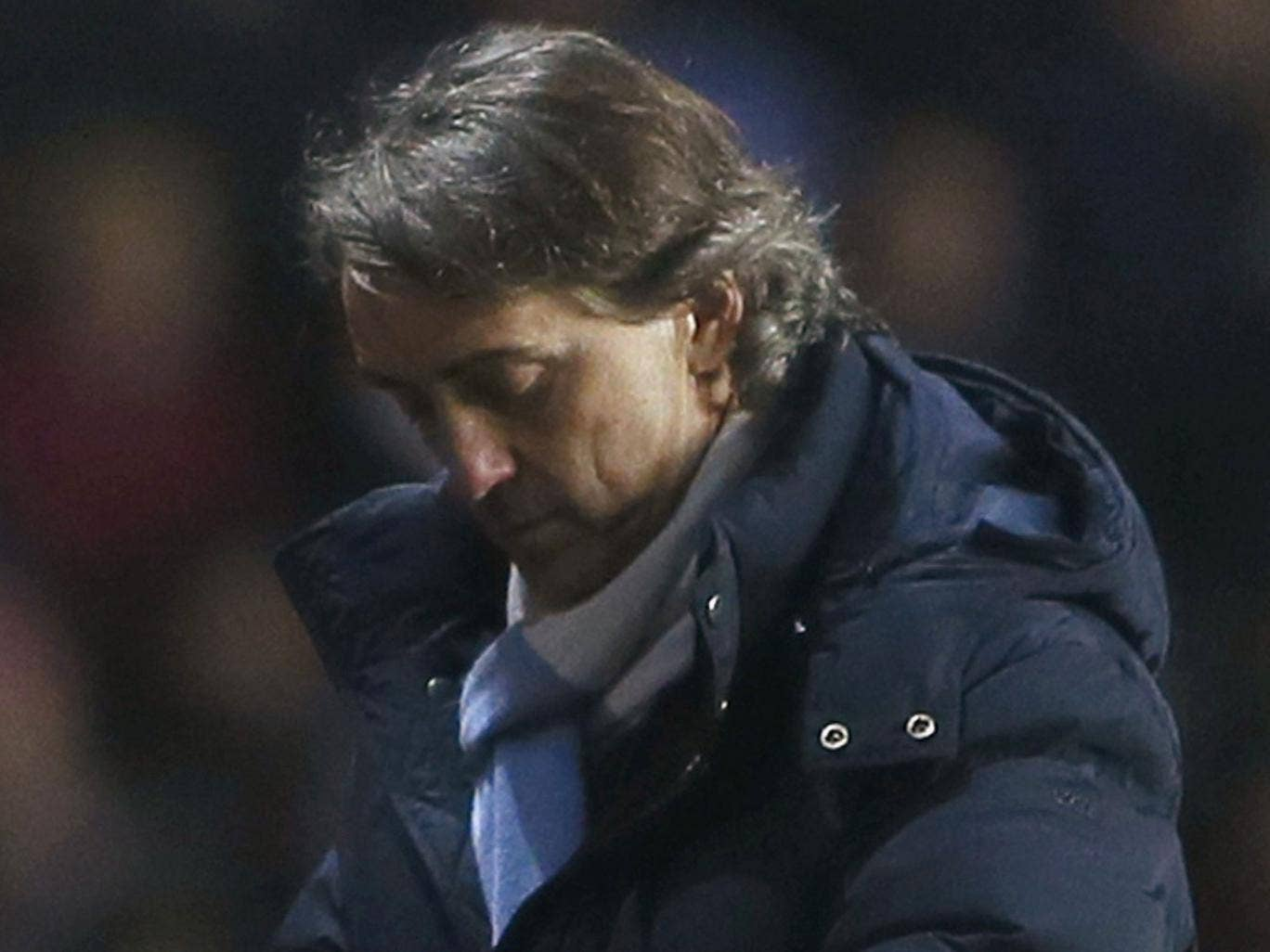 Roberto Mancini admitted that Man City's chances of retaining their title were low and may disappear altogether if Man United win at home to Everton