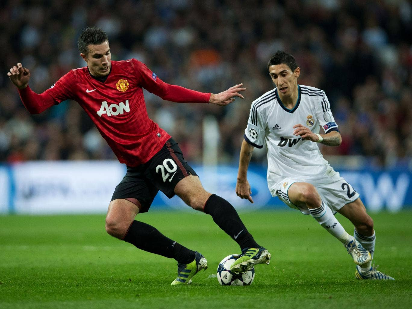 Robin van Persie of Manchester United clashes with Angel Di Maria of Real Madrid