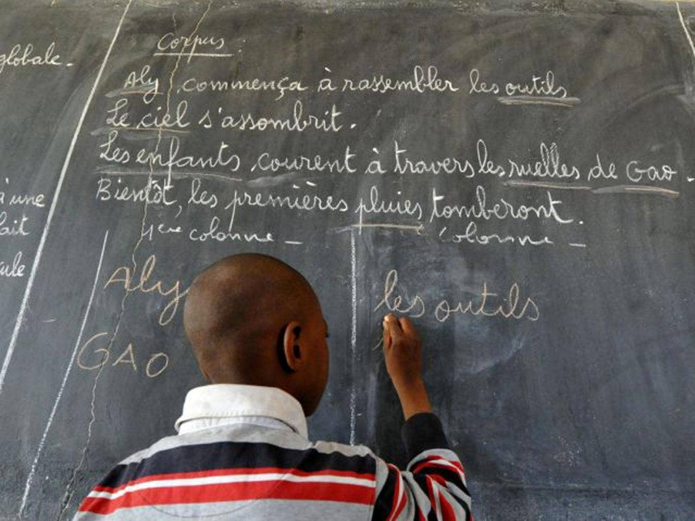 A child writes in French on a classic classroom blackboard