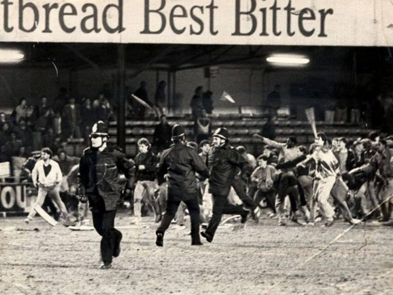 Millwall fans storm past police officers and on to the pitch at Kenilworth Road in 1985