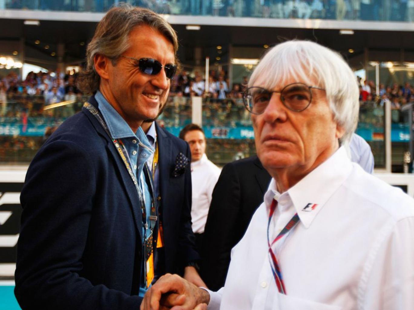 A dapper Roberto Mancini (left) greets Bernie Ecclestone in Dubai