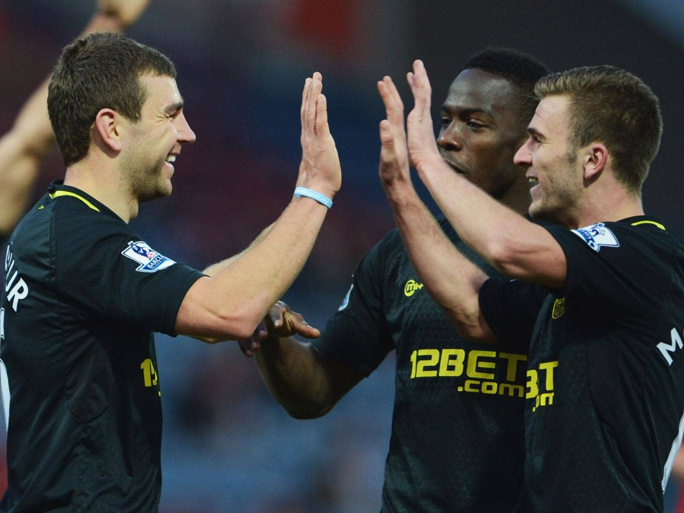 James McArthur of Wigan Athletic (L) celebrates with Maynor Figueroa (C) and Callum McManaman (R) as he scores their third goal