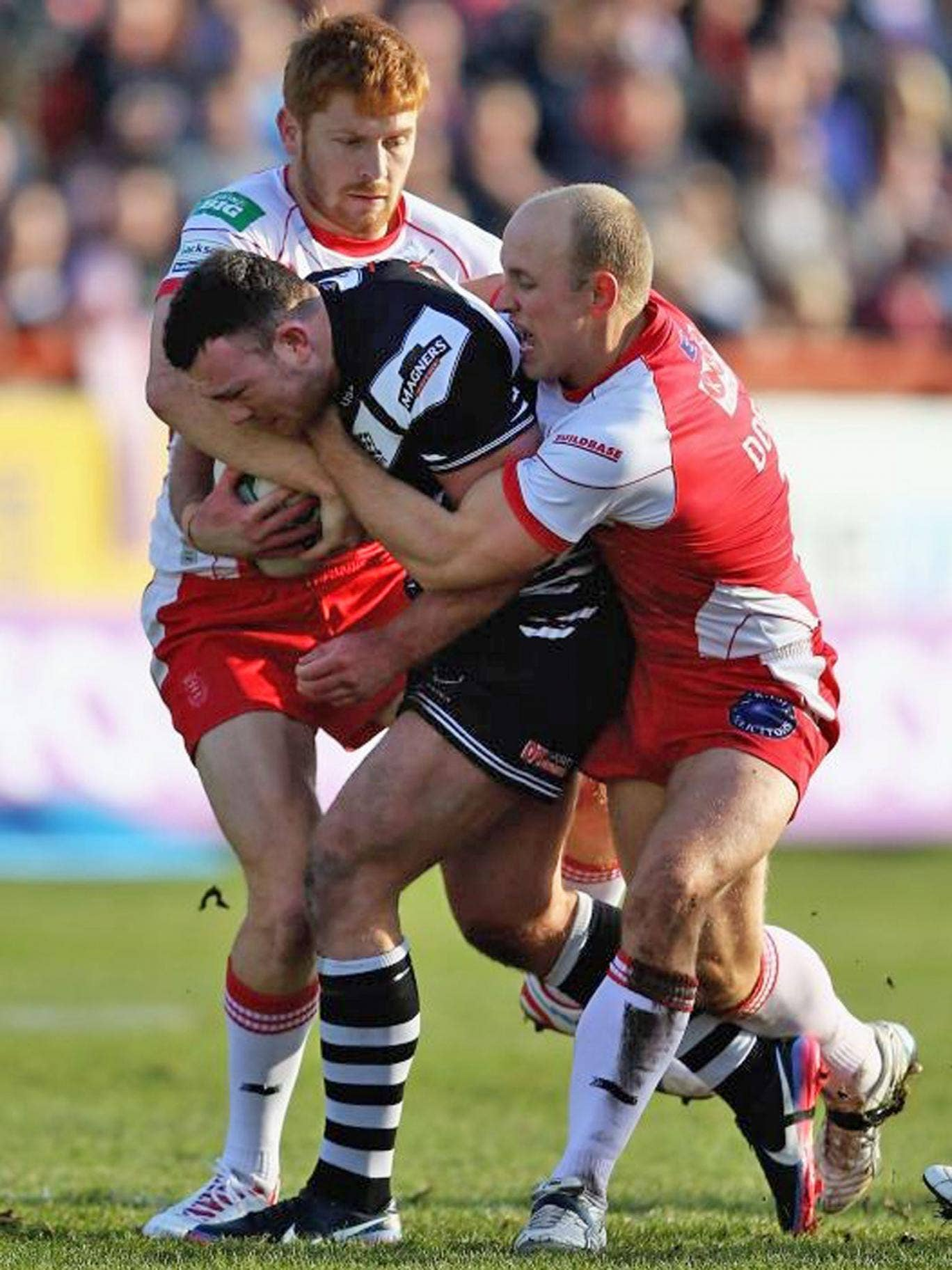 Stefan Marsh, of Widnes, is tackled by Hull KR's Michael Dobson and Kris Welham