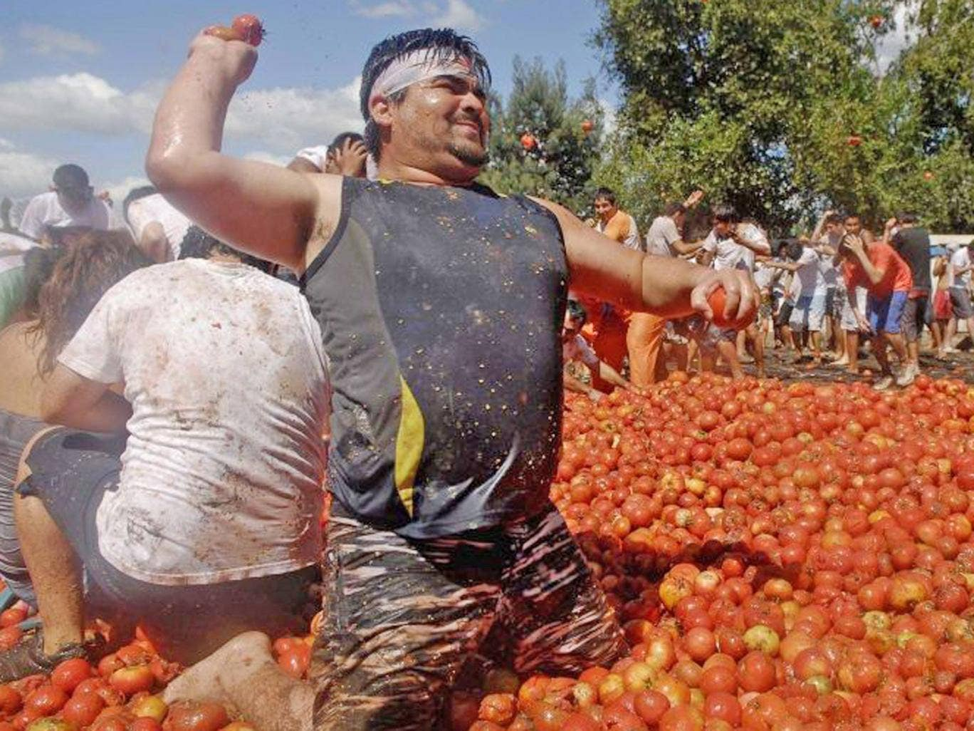 """Revellers play with tomatoes during a """"Tomatina"""" (tomato fight) in Quillon town near Concepcion city, south of Santiago"""