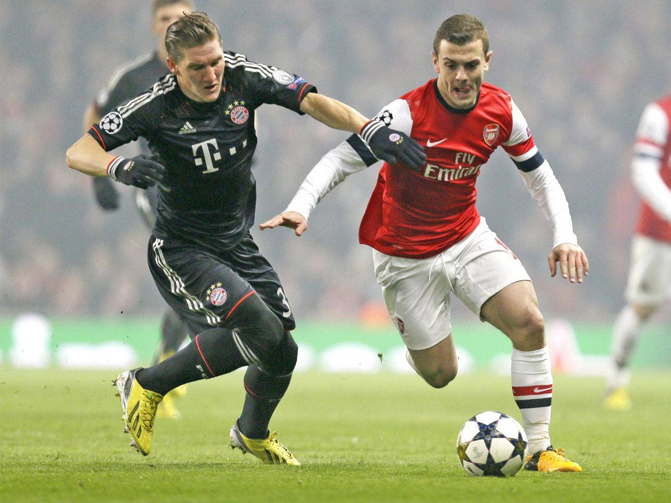 Bastian Schweinsteiger tussles with Jack Wilshere at the Emirates