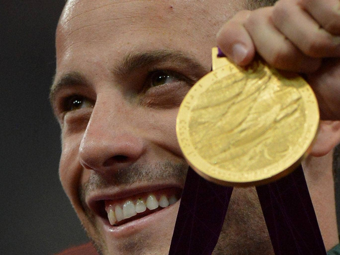 Pistorius celebrates with a gold medal at the Paralympics