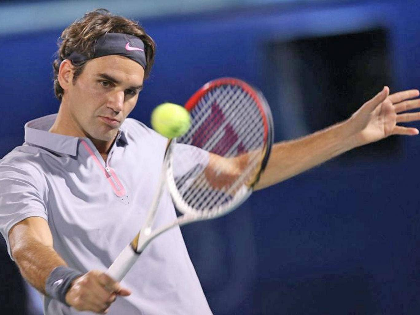 Roger Federer of Switzerland returns the ball to Tunisian Malek Jaziri