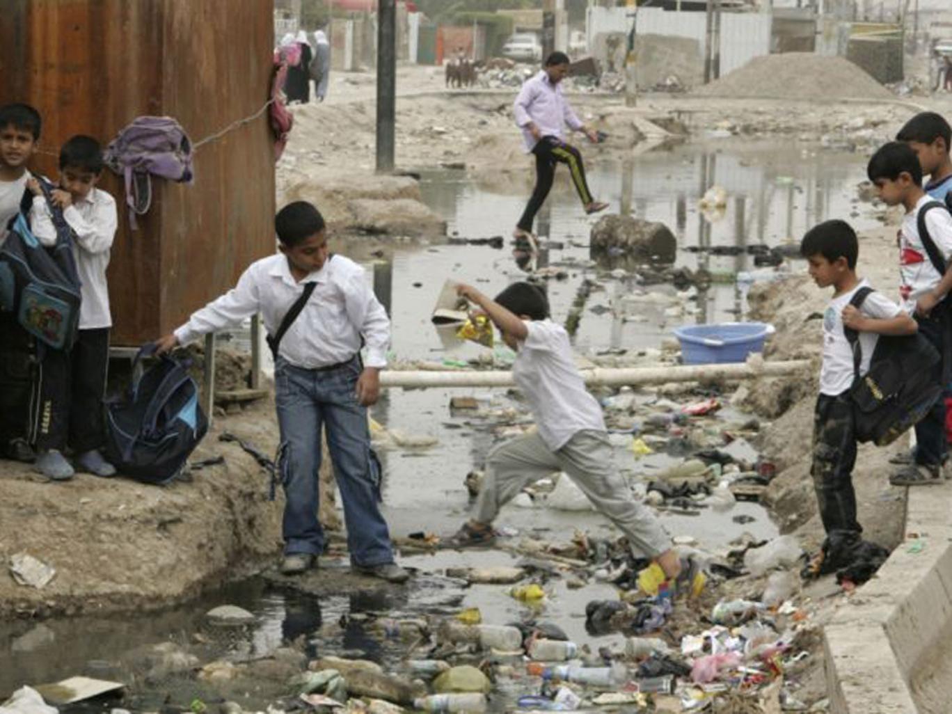 Students cross a sewage canal at Baghdad's Sadr city