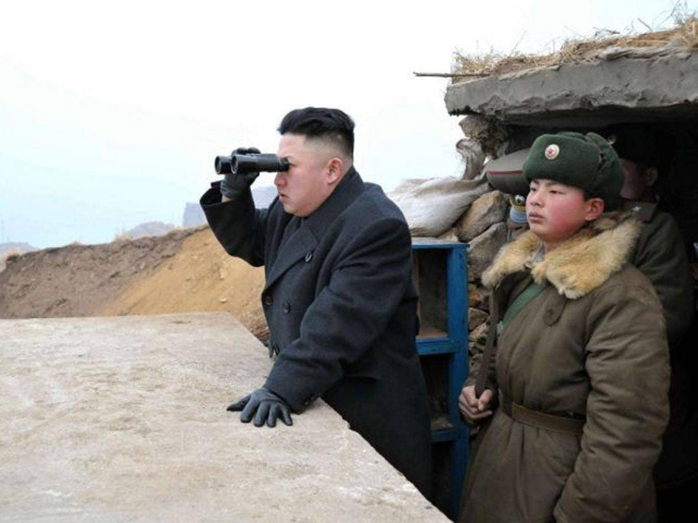 North Korean leader Kim Jong Un, center, uses binoculars to look at the South's territory from an observation post at the military unit on Jangjae islet