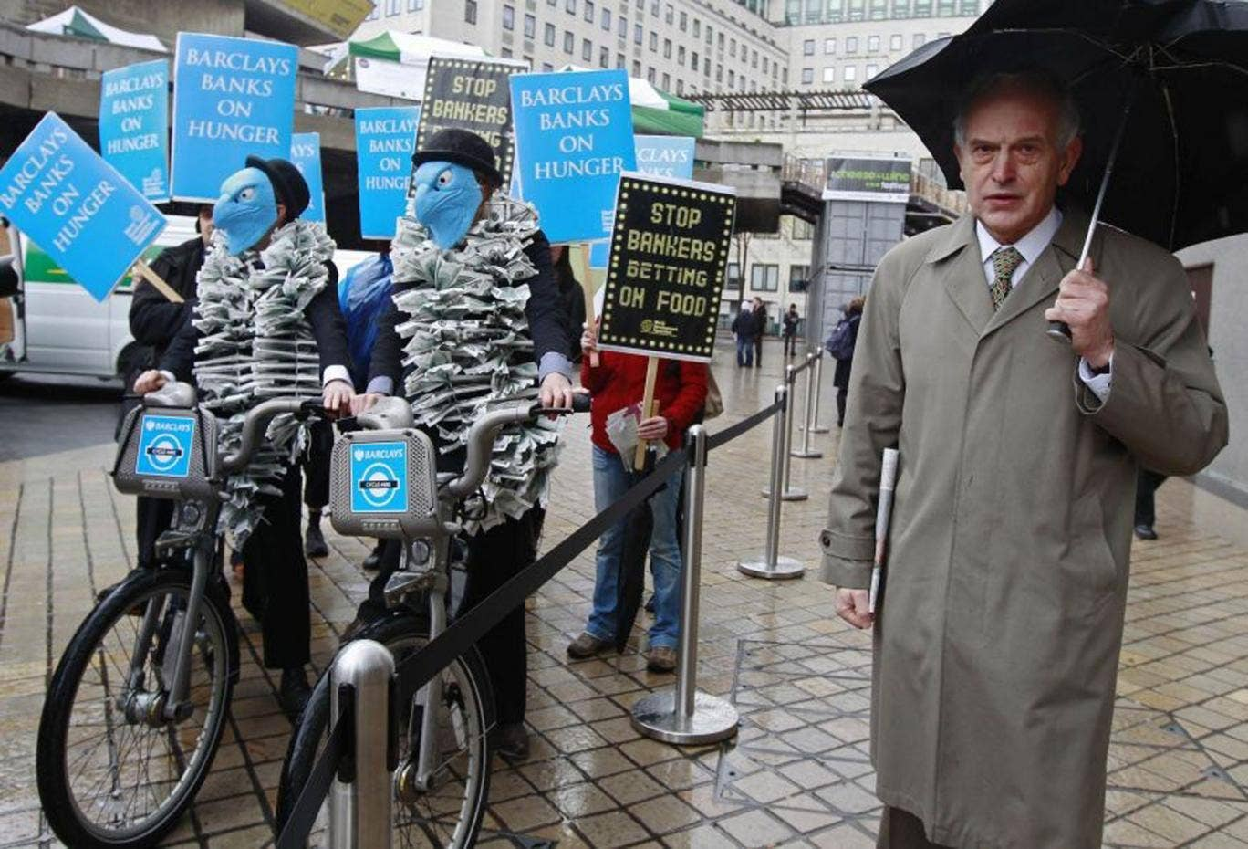 A Barclays shareholder passes demonstrators at the last AGM, where many investors rejected a pay plan