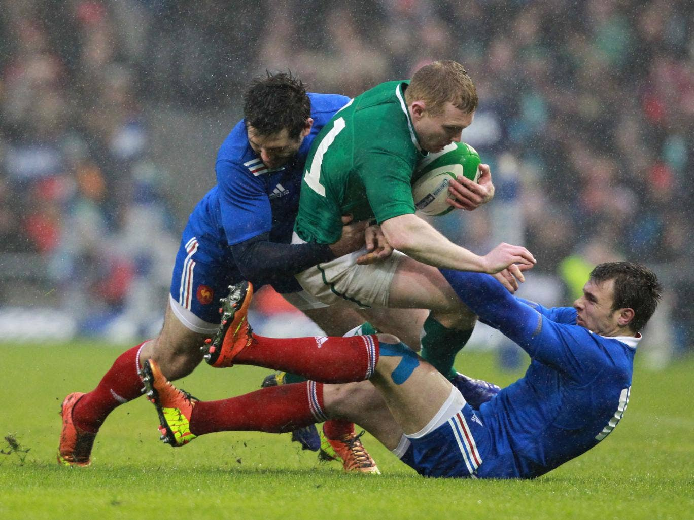 Ireland's wing Keith Earls (C) is tackled by France's wing Vincent Clerc and full back Yoann Huget