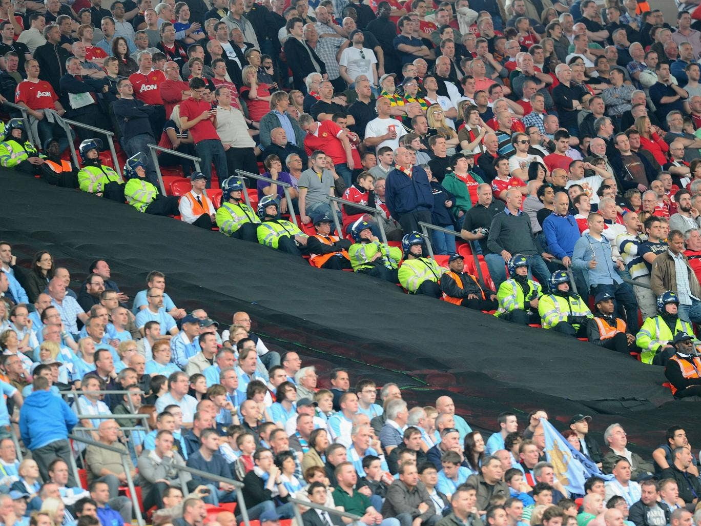 The segregated fans watch the game during the FA Cup sponsored by E.ON semi final match between Manchester City and Manchester United at Wembley Stadium on April 16, 2011