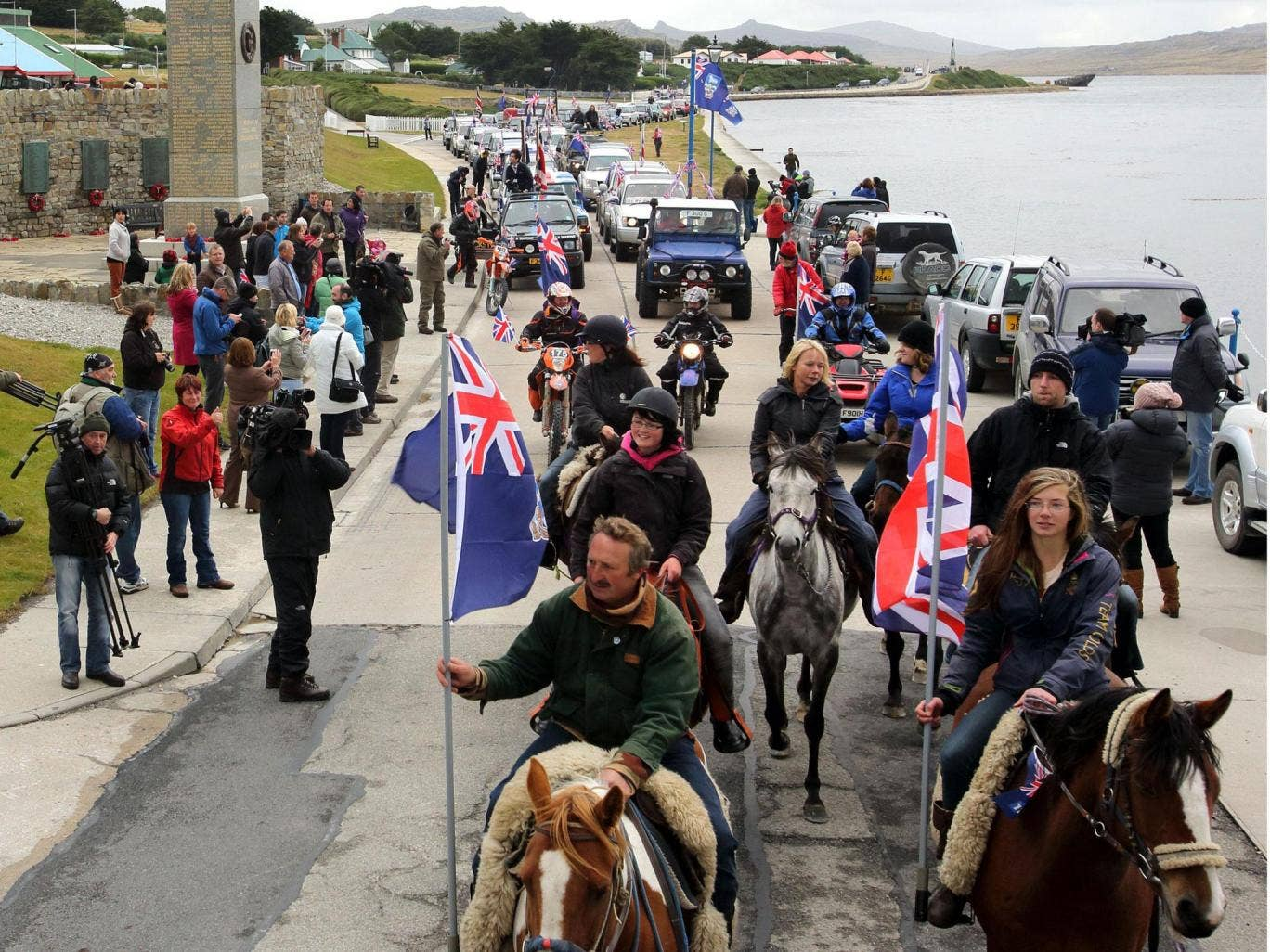 """Islanders taking part in the """"Proud to be British"""" parade pass by the 1982 memorial along Ross Road in Port Stanley"""