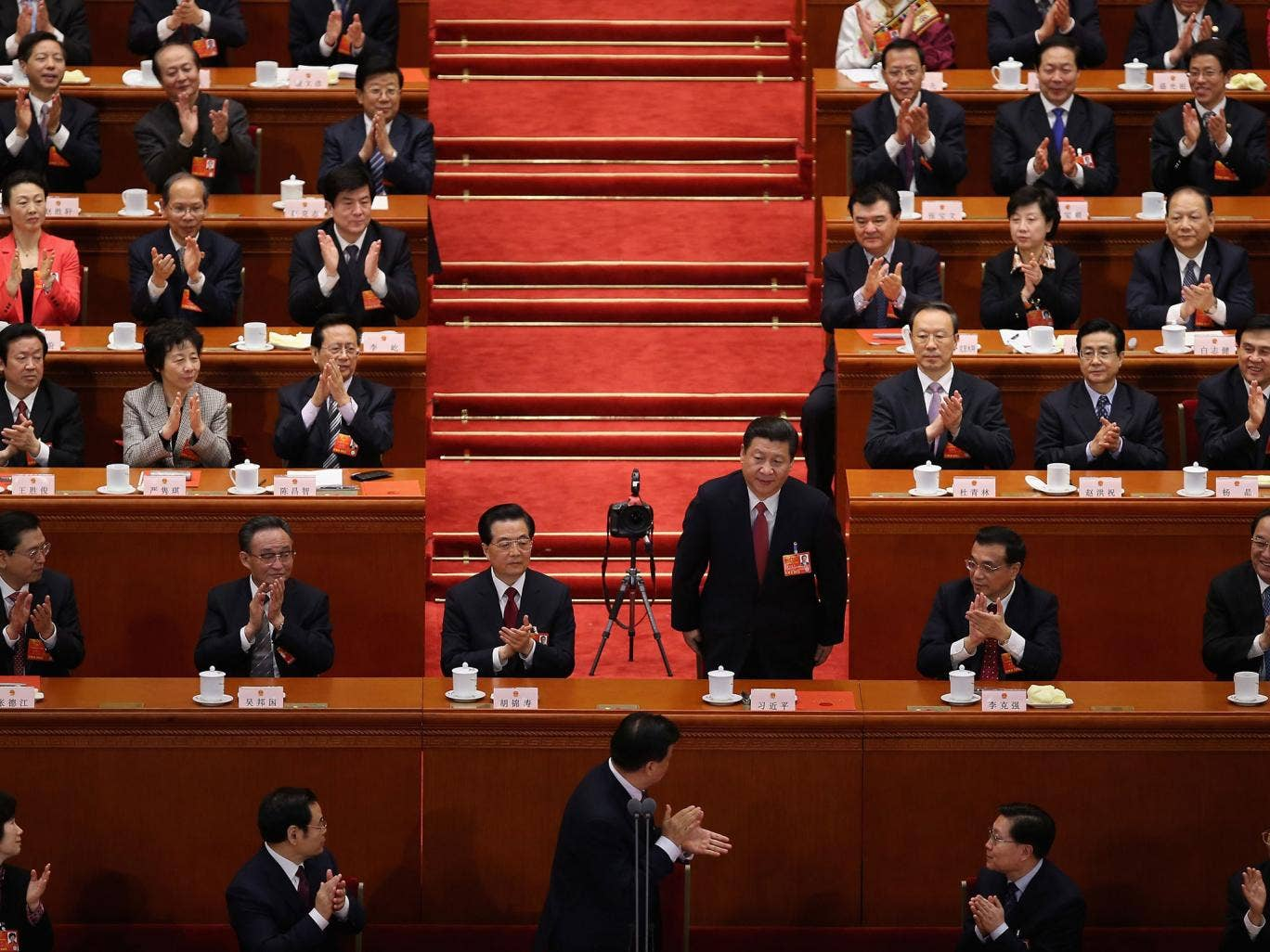 Newly elected President Xi Jinping is applauded by delegates