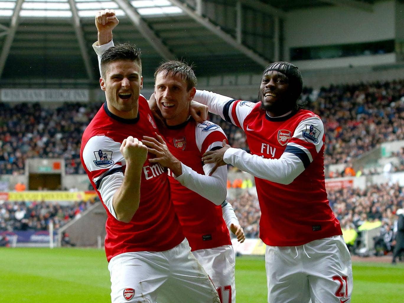 Nacho Monreal of Arsenal (C) celebrates his goal against Swansea with team mates Olivier Giroud(L) and Gervinho
