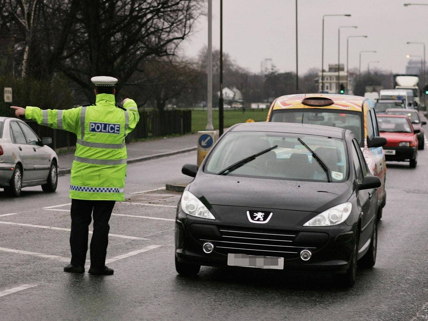 A police pulls a car over as part of a drive to inform motorists of the risk of using a phone while driving