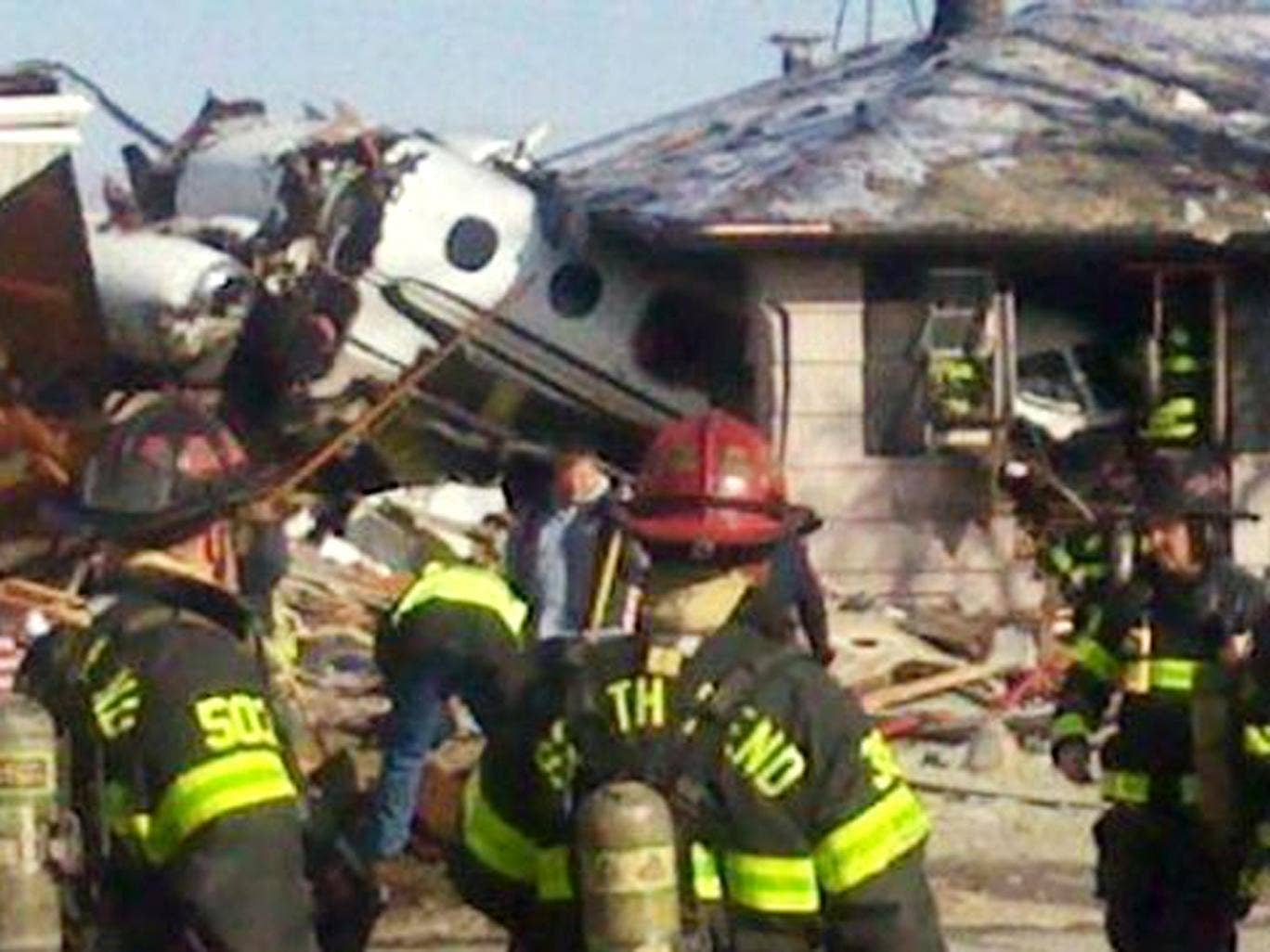 Firefighters and rescue workers look over the scene in South Bend, Indiana, after a small twin-jet aircraft crashed into houses near the airport