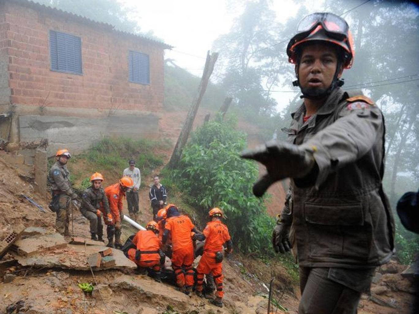 A rescue worker gestures as his colleagues carry the body of a victim of a mudslide in Petropolis, near Rio de Janeiro
