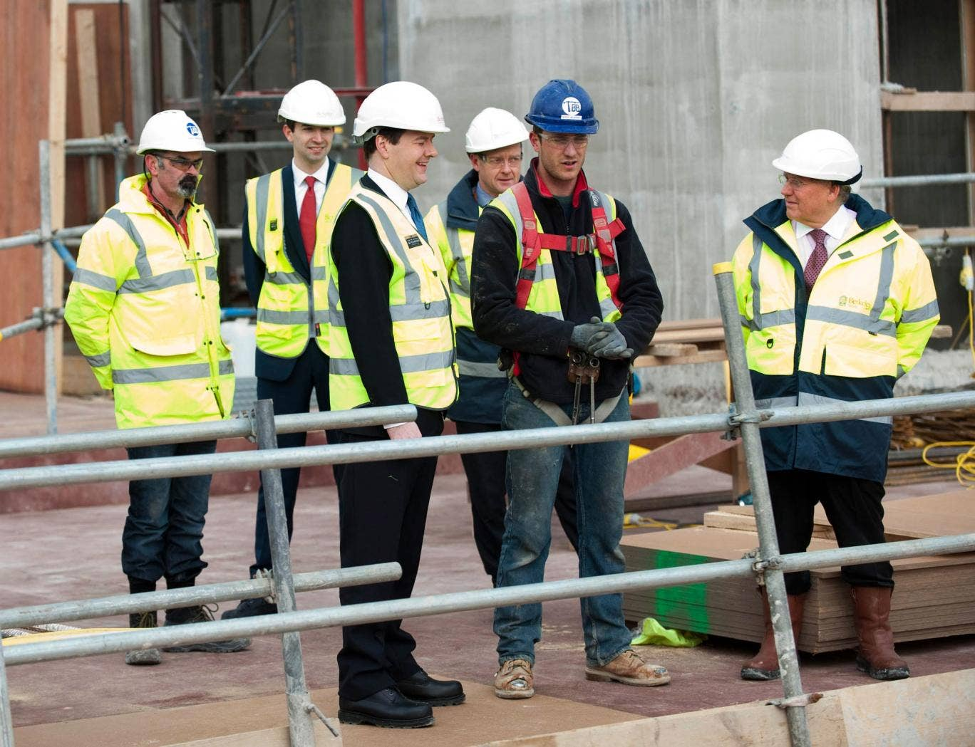 Chancellor George Osborne (3rd left) speaks to construction workers during a visit to the Berkeley Homes Royal Arsenal Riverside development in Woolwich, south London