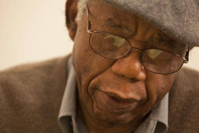 Chinua Achebe writing in his office at Brown University in 2012