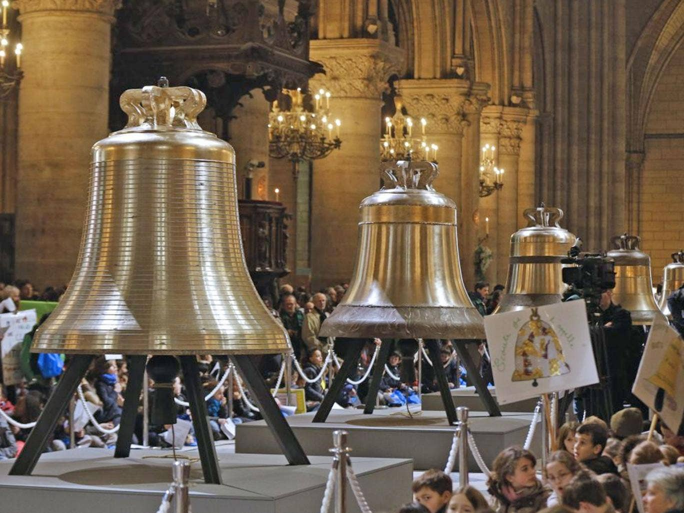 People gather around the new bells of Notre-Dame de Paris Cathedral during their blessing mass