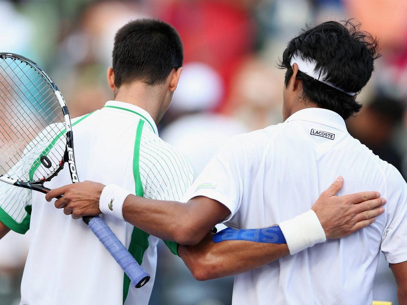 Novak Djokovic of Serbia walks off court after shaking hands at the net after his straight victory against Somdev Devvarma