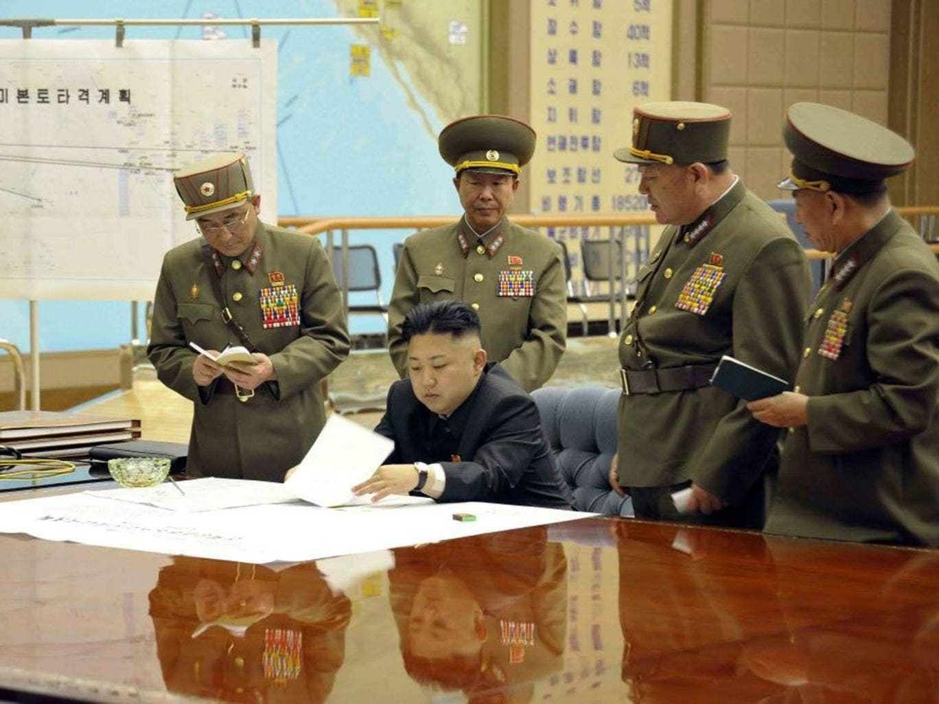A picture released by the North Korean Central News Agency (KCNA) on 29 March 2013 shows North Korean leader Kim Jong-un (sitting) convening an urgent operation meeting