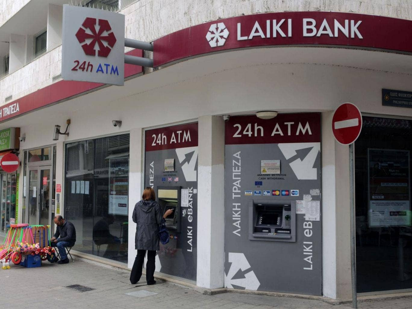 A woman withdraws money from the ATM of a Laiki bank branch