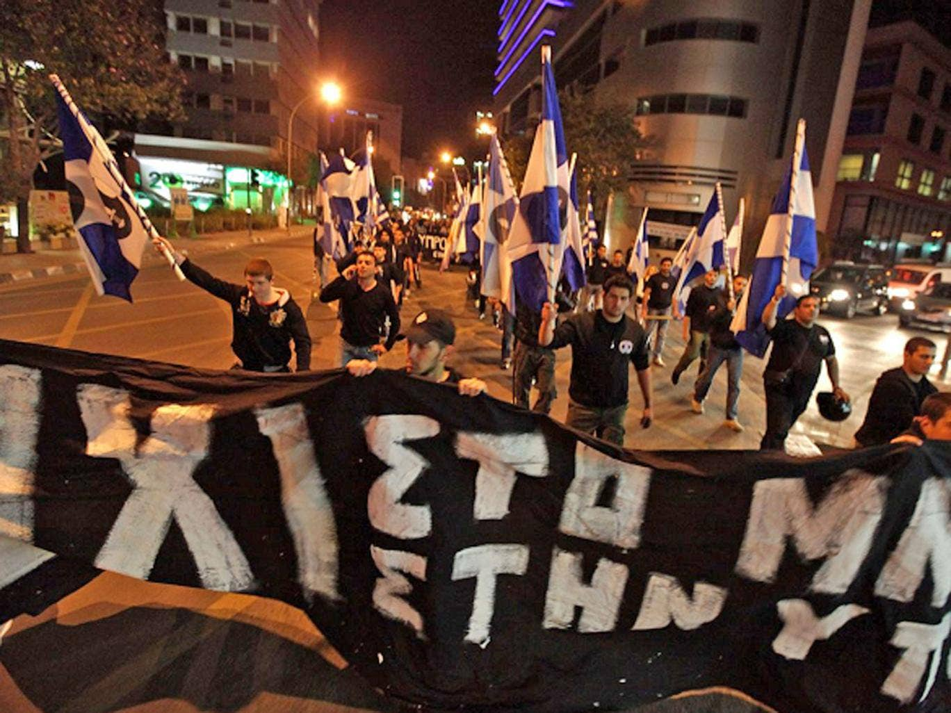 Members of the nationalist Cypriot party Elam (National Popular Front) march with a banner during a protest against the measures imposed on the banking sector