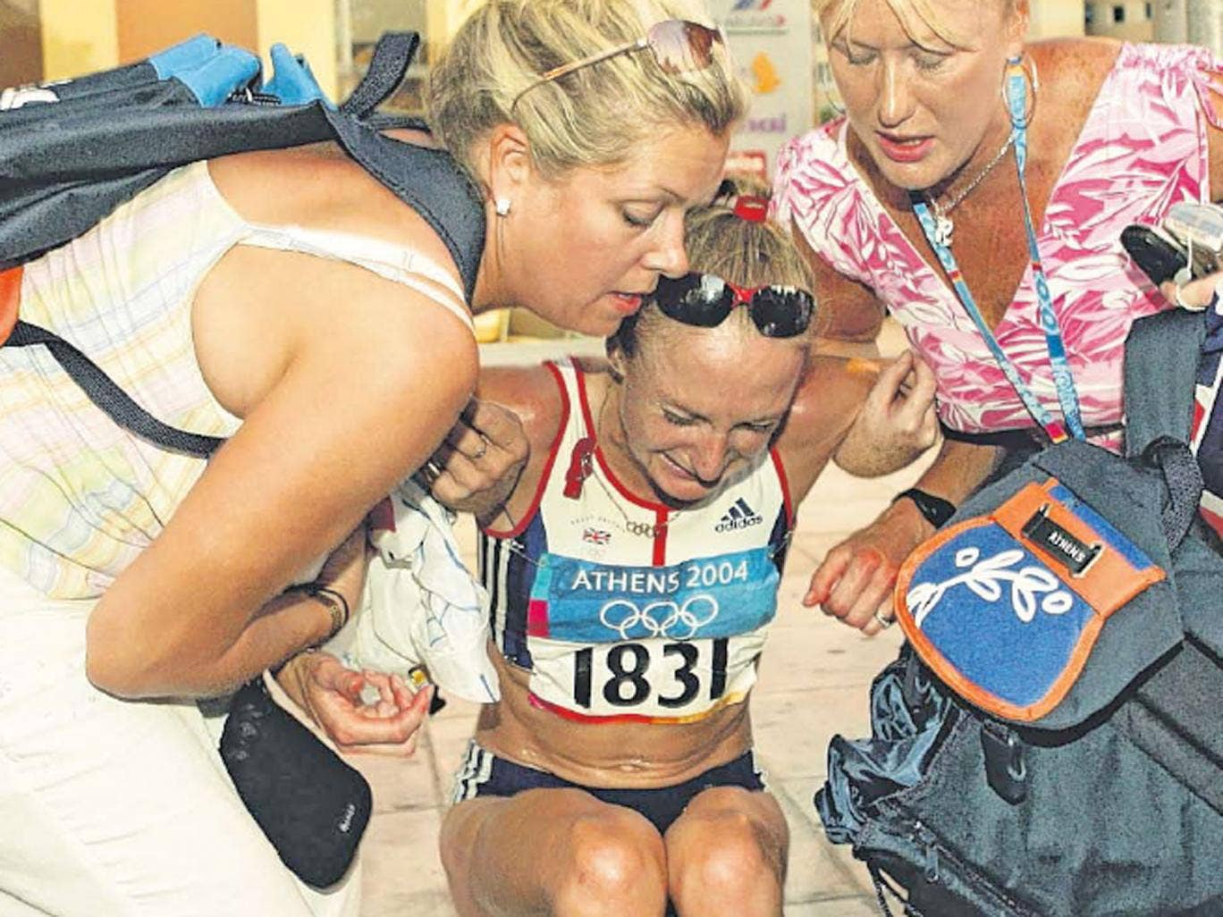 Paula Radcliffe is helped up after pulling out of the women's marathon at the Athens Olympics