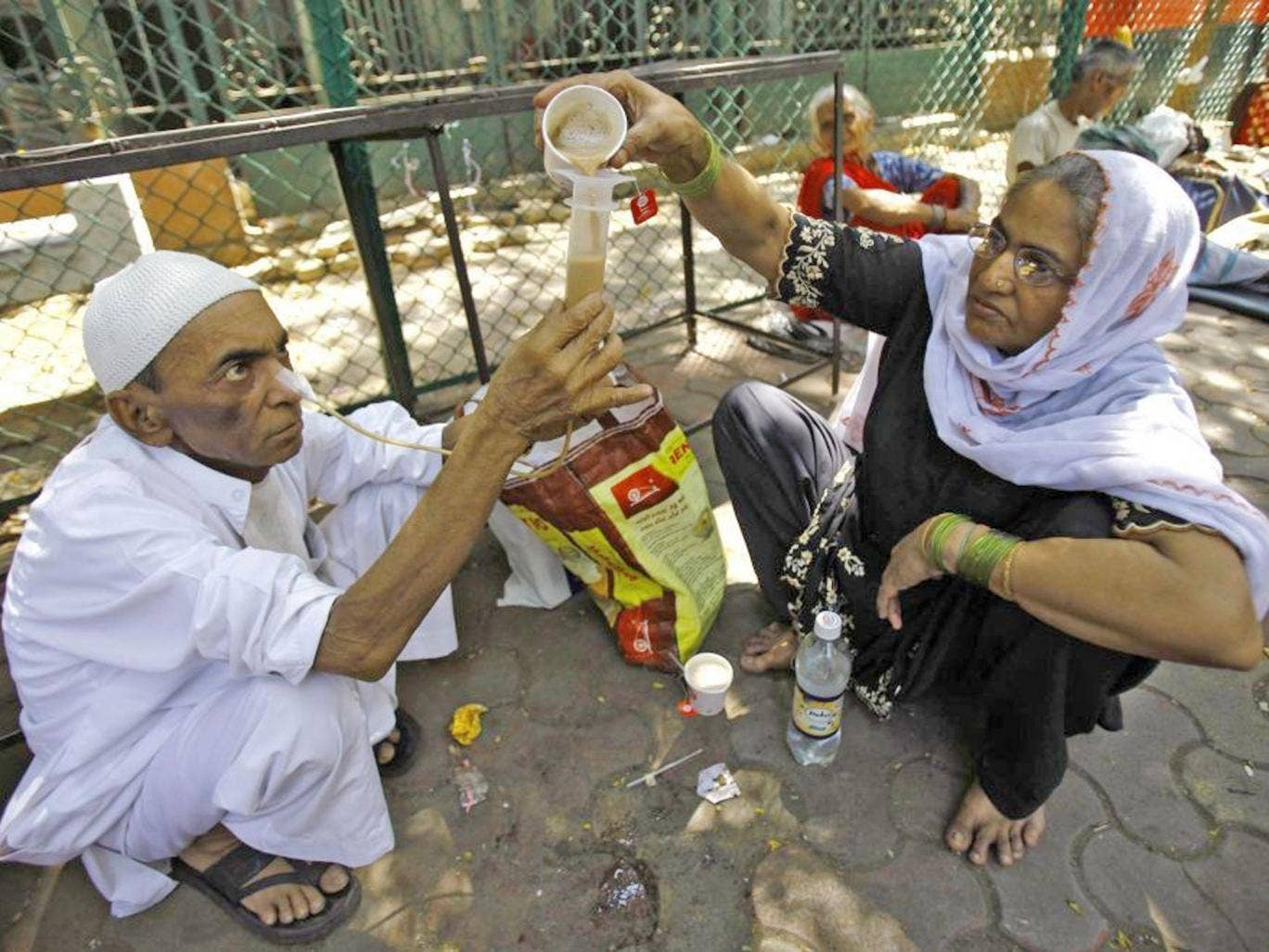 Kamal Ahmad, 68, who is suffering from throat cancer, gets help from a relative to drink tea through his nose outside Tata cancer hospital in Mumbai, India