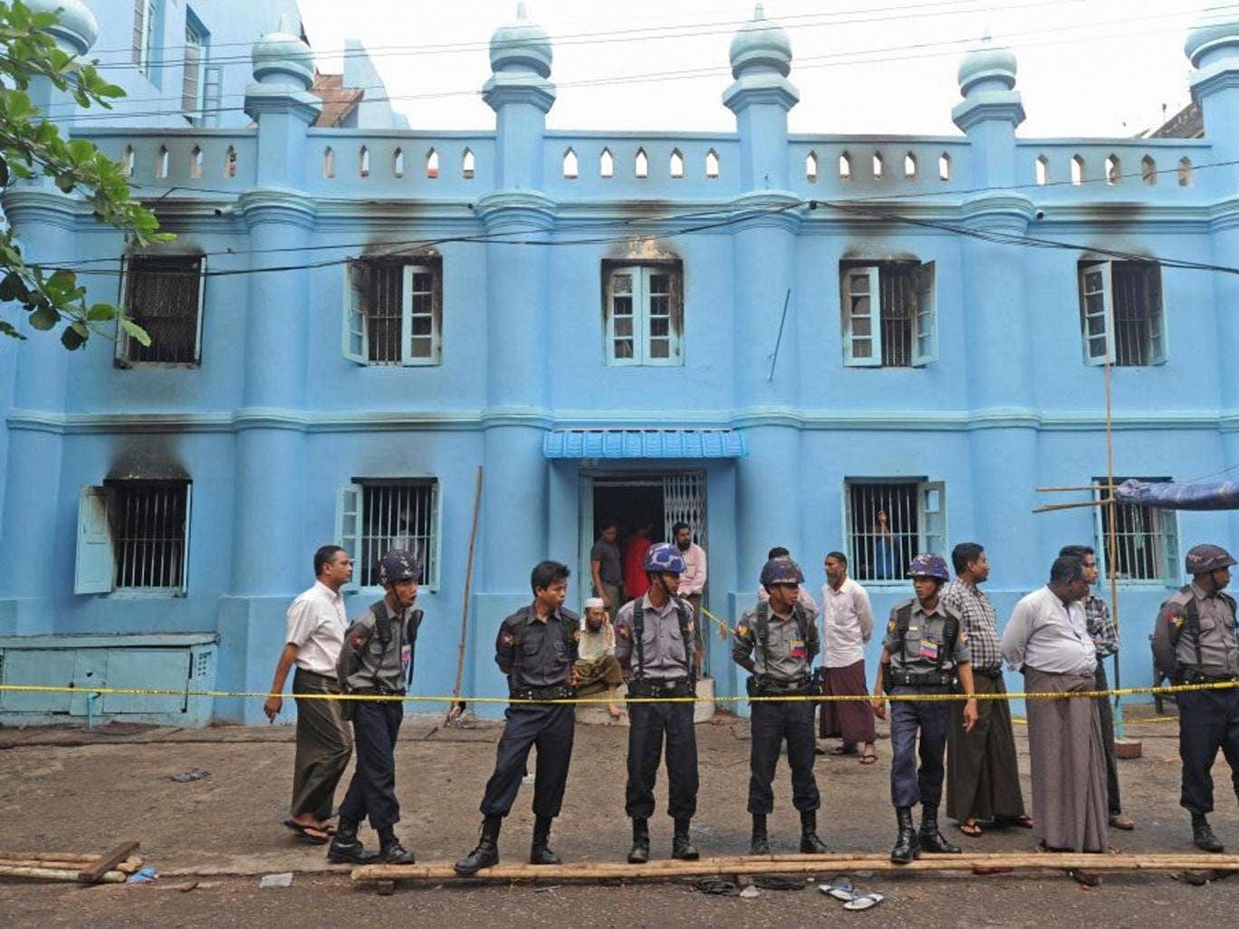 Police officers stand guard outside the mosque in Yangon following the fire
