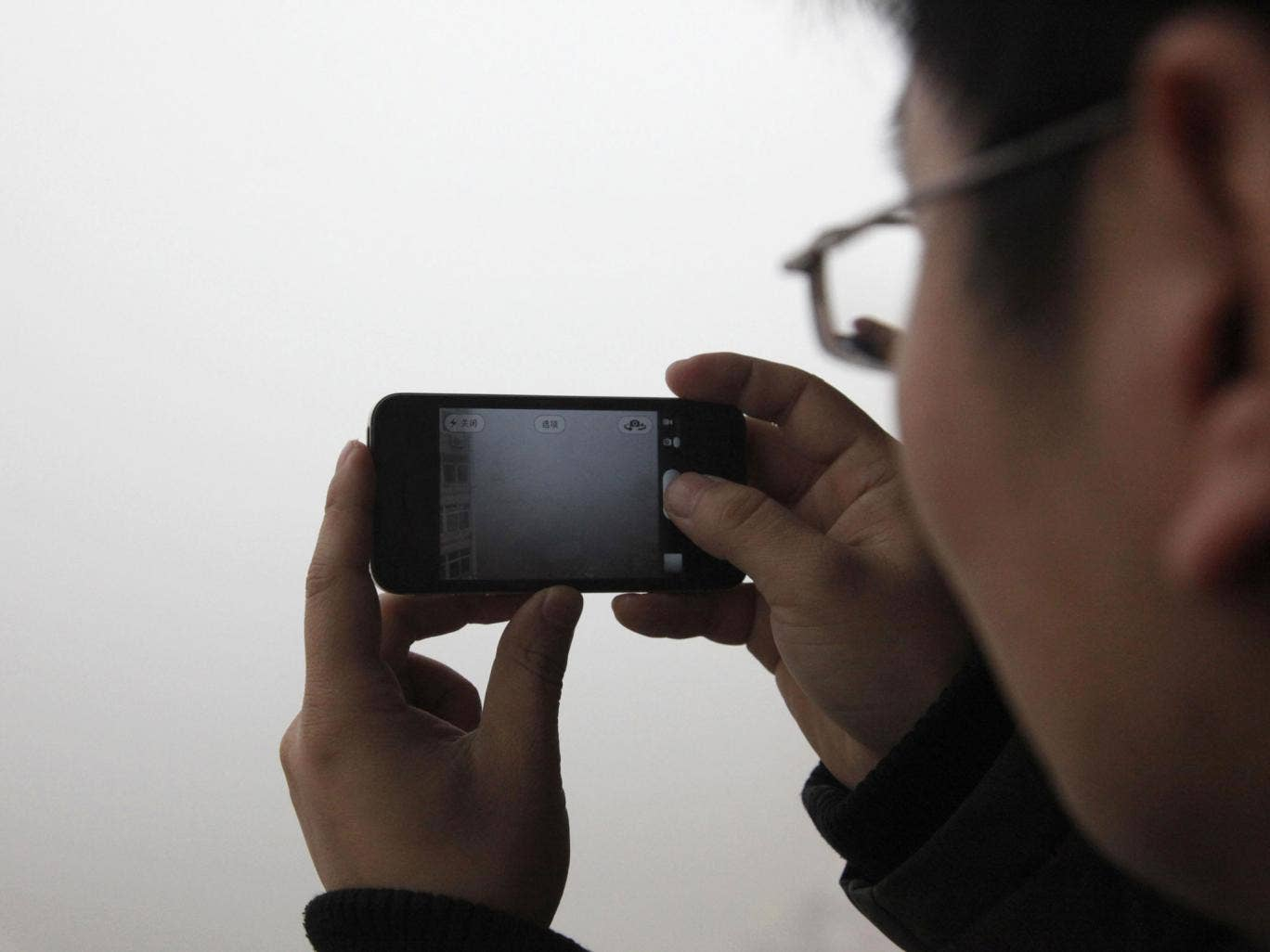 A man takes a photo of heavy smog in Qingdao, east China's Shandong province