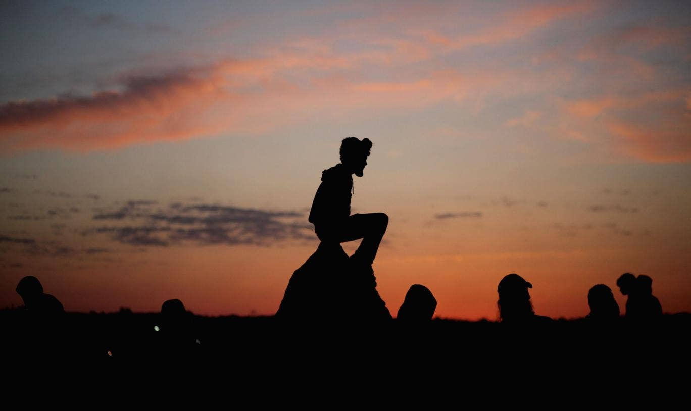 Glastonbury romance? Revellers watch the sunrise from the stone circle during the festival