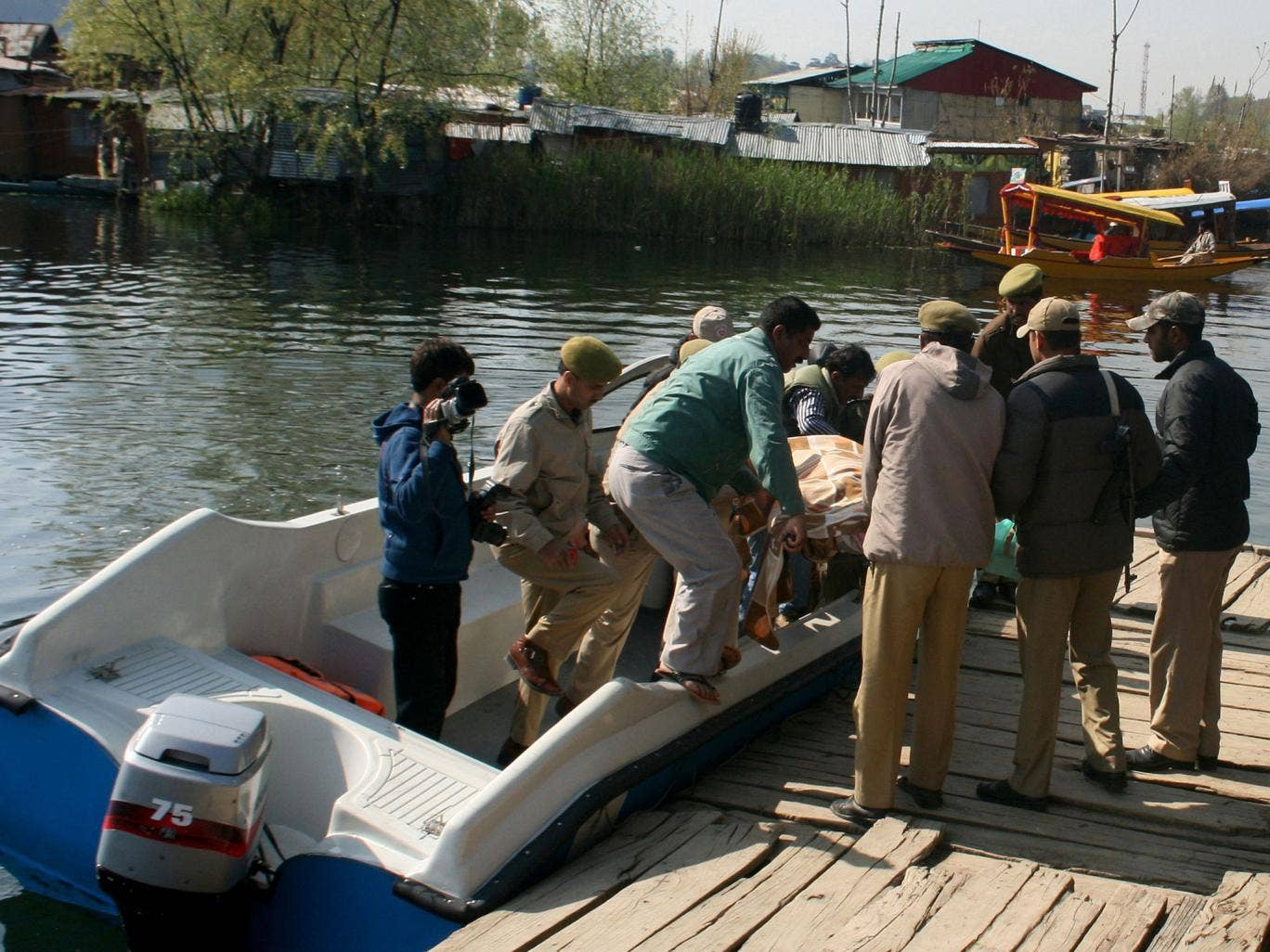 Indian police move the body of the British woman from a boat at Dal Lake in Srinagar